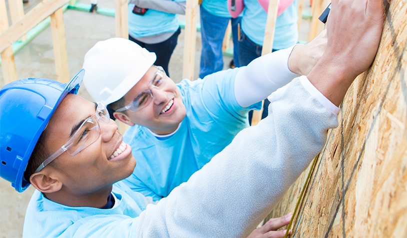 Image of two volunteers building a home.